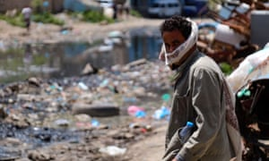 A man wears a face covering beside a rubbish-strewn street in Yemen's third city of Taez