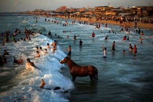 Gaza StripA Palestinian man washes his horse in the waters of the Mediterranean Sea as people swim on a hot day