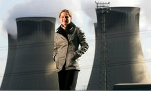 Dorothy Thompson  in a short coat with huge cooling towers in the background