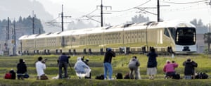 Trainspotters watch the 10-car vehicle cross a field in Nikko, north-east of Tokyo
