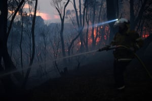 A NSW Rural Fire Service firefighter conducts property protection as a bushfire burns close to homes on Railway Parade in Woodford, NSW
