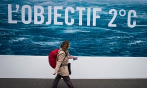 A woman walks in front of a poster saying 'Objective 2 degrees'