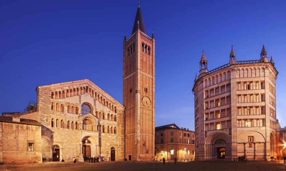 The Duomo and Battistero in Parma illuminated at dusk.