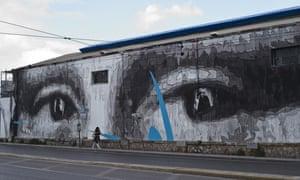 A woman walks by a giant mural by Greek street artist iNO depicting the eyes of Leonardo da Vinci's Mona Lisa, in Athens.