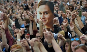 A photograph of Jo Cox is held aloft at a gathering in London following her death.