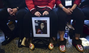 An attendee of the closing ceremony for the National Inquiry into Missing and Murdered Indigenous Women and Girls holds a photo of a lost family member in Gatineau, Quebec, on 3 June.