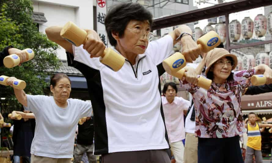 Older people work out with wooden dumb-bells in the grounds of a temple in Tokyo