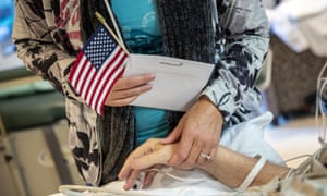 A woman visits her Native American army veteran father. Native American officials have voiced concerns that the coronavirus outbreak could overwhelm tribal health services.
