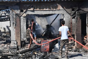 Camping and caravanning site owners try to extinguish a fire burning in Bormes-les-Mimosas