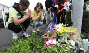 People pray for victims outside the Kyoto Animation building.