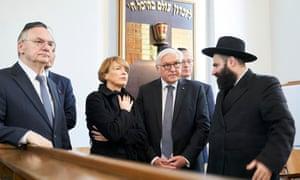 The German president, Frank-Walter Steinmeier, (second right) and his wife, Elke Buedenbender, speak with Rabbi Elisha Portnoy in Halle on Thursday.