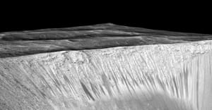 Dark narrow streaks called recurring slope lineae emanating out of the walls of Garni crater on Mars. The dark streaks here are up to few hundred meters in length. They are thought to be formed by flow of briny liquid water on Mars.