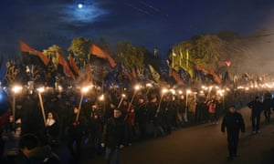 Ukrainian demonstrators carry flags and torches during a rally in Kiev on 14 October 2016.