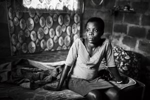 Paulina, 19, sits in the room she shares with other family members in Nyaje village