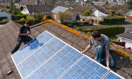 Two men fitting solar panels on a pitched roof