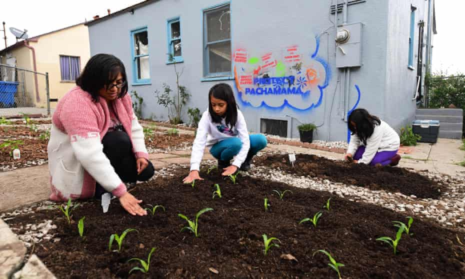 Martha Escudero, left, plants corn in the backyard of her reclaimed home with her daughters Meztli, right, and Victoria.