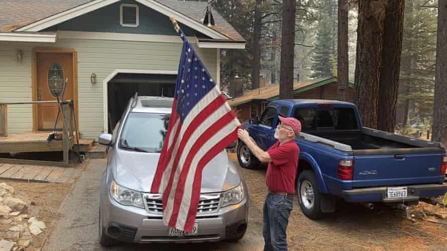 Bill Roberts rolls up an American flag in front of his house in South Lake Tahoe.