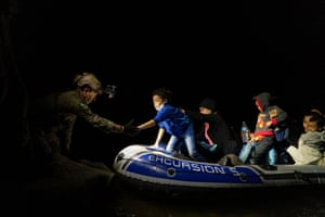 Roma, Texas, USAsylum-seeking migrants' families attempt to disembark from an inflatable raft with the help of a Texas ranger after crossing the Rio Grande river from Mexico to the US.