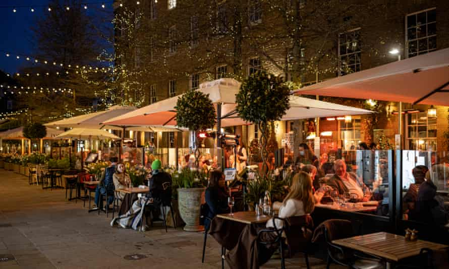 Diners eating outdoors at a restaurant in London.