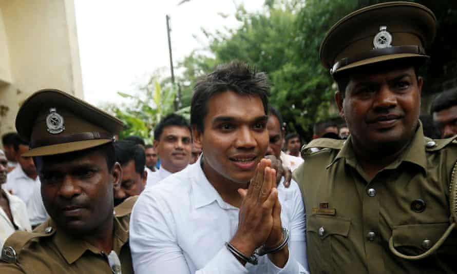 Namal Rajapaksa, son of the former Sri Lankan president Mahinda Rajapaksa, leaves court with prison officers.