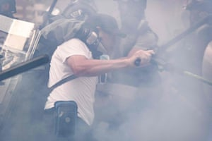 A protester is detained by police amid teargas