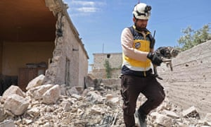 A member of the White Helmets rescue organisation carries a cat amid the rubble of a partially destroyed building in Idlib province