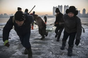 Workers pull a large block of ice