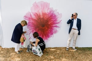 Visitors stand by flower-decorated hoardings
