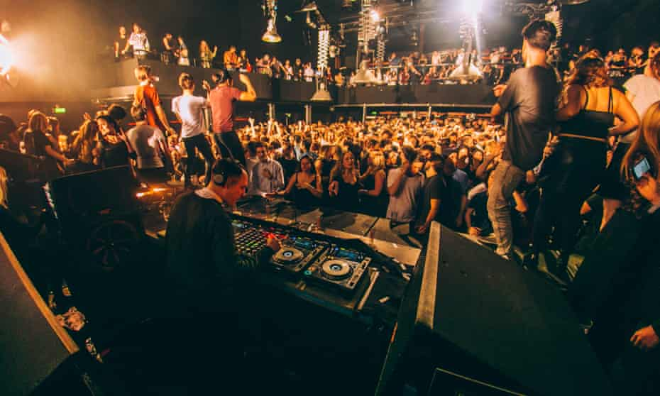 A crowd of dance music fans on the dancefloor at Amsterdam club De Marktkantine. The image is taken from behind the DJ booth, where a DJ is using digital decks to play music.