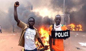 Protesters pose with a police shield outside the parliament in Ouagadougou in Burkina Faso.