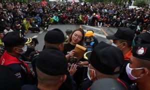 Student leader Panusaya Sithijirawattankul hands over a letter to royal guard police in Bangkok on Sunday with demands for reforming the monarchy.