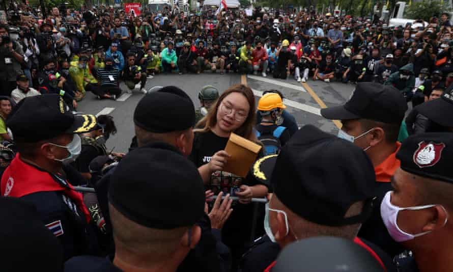 Student leader Panusaya Sithijirawattanakul hands over a letter to royal guard police in Bangkok on Sunday with demands for reforming the monarchy