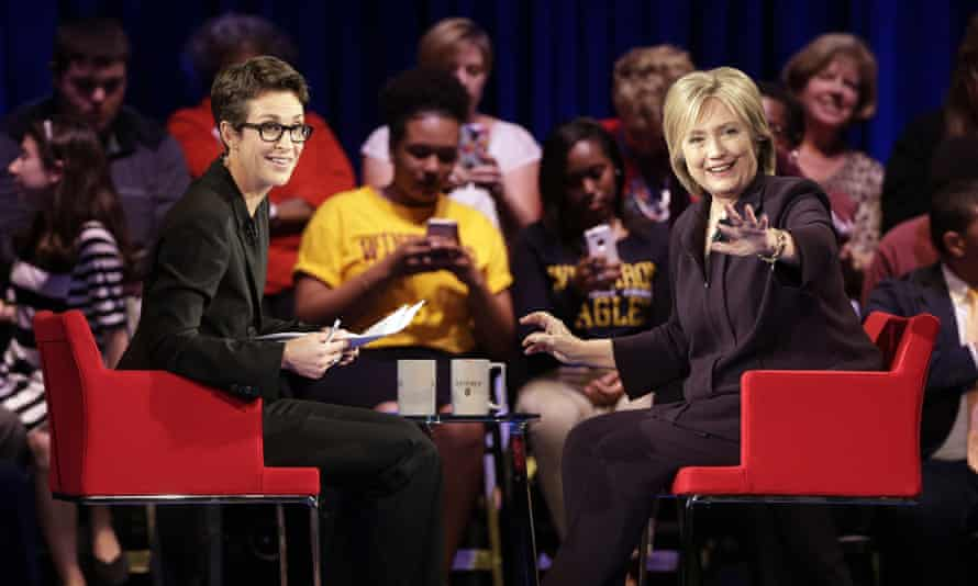 Hillary Clinton, right, waves to the crowd as MSNBC's Rachel Maddow, left watches.