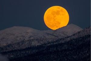 The moon seen over hills near the city of Yuzhno-Sakhalinsk on Sakhalin Island, Russia