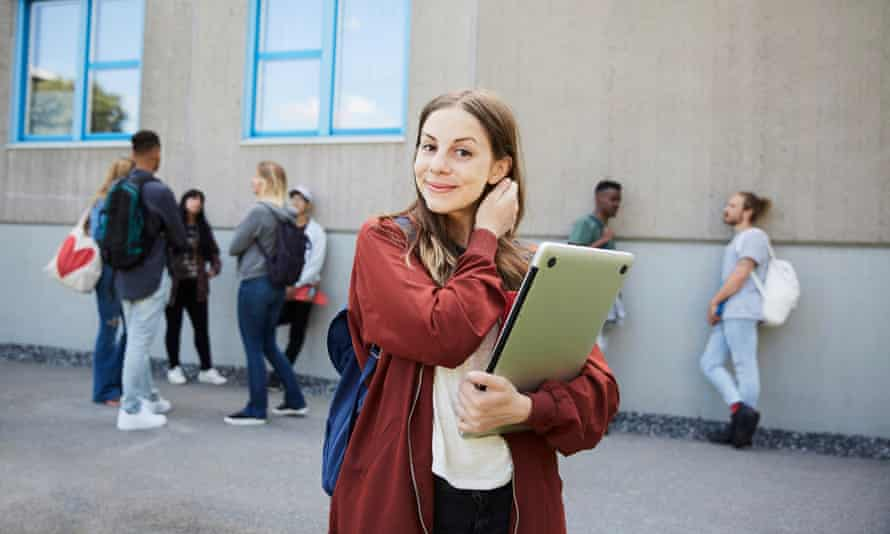 Portrait of smiling female student carrying laptop while standing at university campus with friends in background