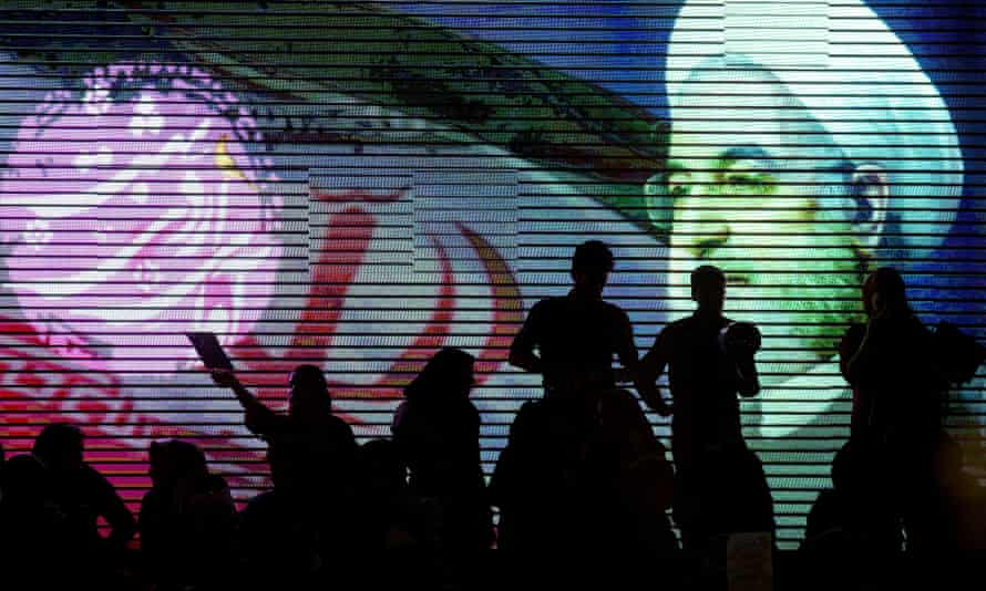 Silhouettes of people against a huge projection of Rouhani's face