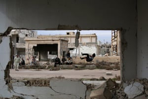 Parkour coach Ibrahim al-Kadiri, 19, is seen demonstrating his Parkour skills from a damaged building as people watch him in the rebel-held city of Inkhil, west of Deraa, Syria, February 4, 2017.