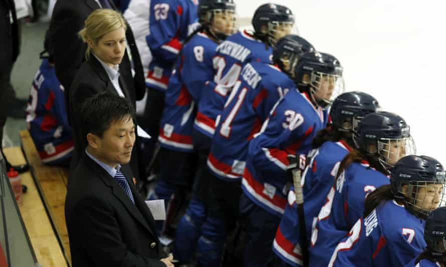 Pak Chol Ho, the coach of North Korea's women's ice hockey team, and Sarah Ruth Murray, the head coach of the South Korean team, watch the women's ice hockey friendly match at Seonhak International Ice Rink on 4 February