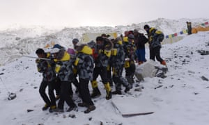 Rescuers carry an injured person to a helicopter at Everest base camp.