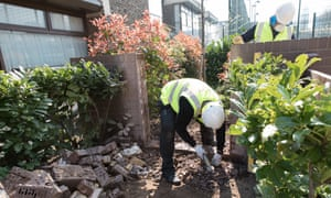 Following a Guardian Cities investigation, Henley Homes workers remove the wall at Baylis Old School development in Lambeth, London, which residents claimed excluded children of social housing from using shared playgrounds.
