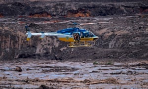 Rescuers in a helicopter search for survivors after the collapse of a mining dam near the town of Brumadinho, Brazil.