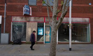 A man walks in front of a derelict shopfront in Barrow-in-Furness, Cumbria