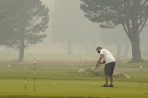 A golfer wears a face mask as he practices his putting at the smoke-shrouded Lake Tahoe Golf Course in South Lake Tahoe.
