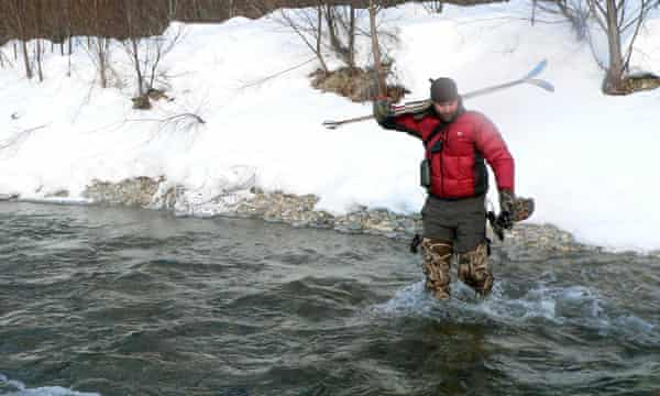 Jonathan Slaght crosses a shallow channel of the Serebryanka River in Primorye, Russia. Working with fish owls in winter often requires odd equipment combinations such as neoprene hip waders and backcountry skis.