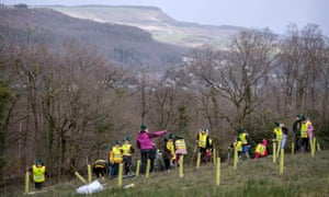 Children and staff from Blaendulais primary school in Seven Sisters plant trees during the national forest launch above Neath in South Wales