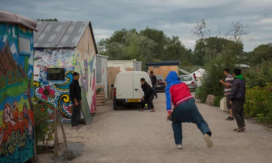 Young refugees in the Calais camp play cricket