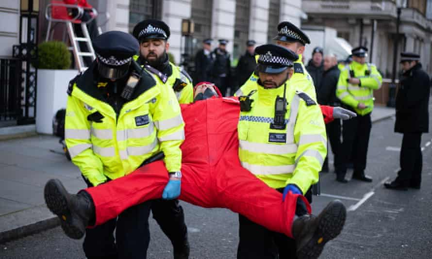 Police remove a Greenpeace activist after the environmental group blockaded the BP headquarters with solar panels and oil barrels,