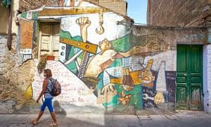 Female tourist walks past street art murals in Orgosolo, Sardinia, Italy.