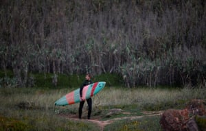 A surfer carries his surf board after a surf session