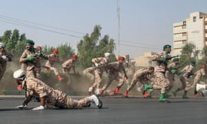 Iranian soldiers jump over a hedge at a street as they run for cover during the terrorist attack.